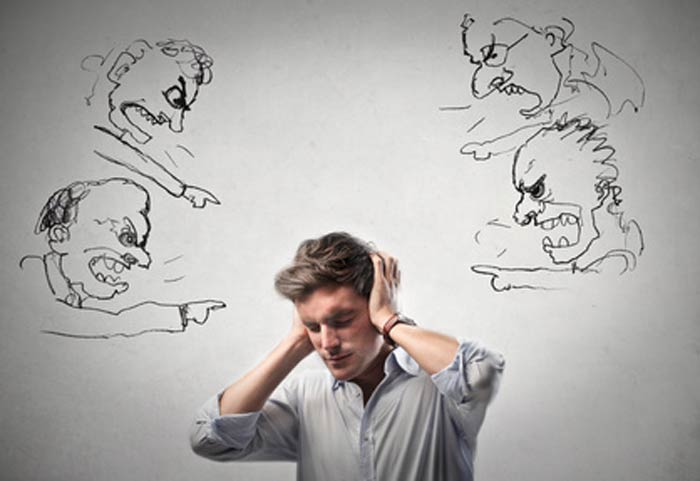 person clutching his head with both hands because he can't stand the inner turmoil, the inner critics tormenting him
